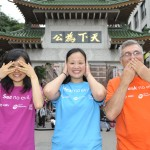"Jennifer Chen, President of Harvard Team HBV (left), Melissa Wong, Chair of the Board of Directors at MAP for Health (center), and Dr. Salim Kabawat, Medical Director at Quest Diagnostics (right) perform the ""see no evil, hear no evil, speak no evil"" actions in front of Chinatown Gate."