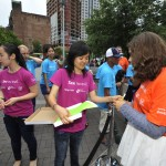 Jennifer Chen, President of Harvard Team HBV, passes out wristbands to keep track of number of participants